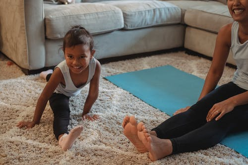 Smiling ethnic girl doing splits on fluffy carpet near joyful young mother sitting on yoga mat in light living room