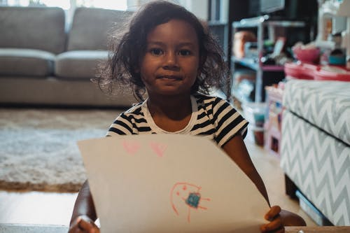 Ethnic girl showing drawing in living room