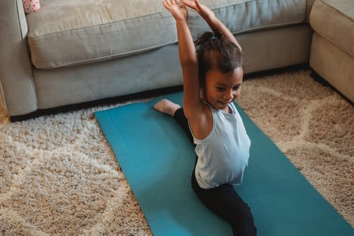 From above of cheerful little ethnic girl in sportswear doing leg split on stretch mat with raised hands at home