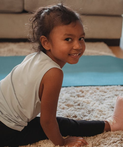Cute girl stretching on carpet