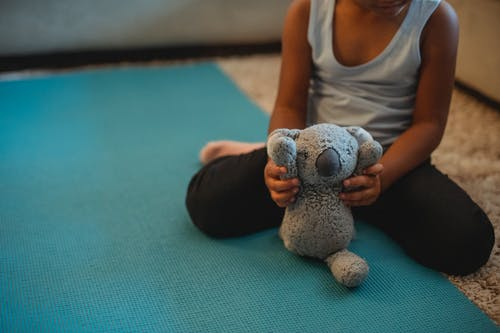 Crop anonymous barefoot ethnic child playing with koala bear toy sitting on stretch mat at home