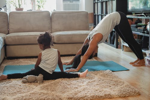 Unrecognizable female and little girl in sportswear stretching on carpet and stretch mat in living room