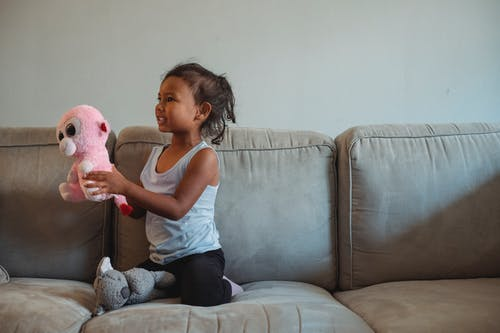 Cute girl with toys on couch