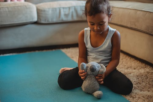 Focused Hispanic girl in activewear playing with toy on floor and looking down