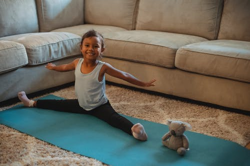 Cheerful little ethnic little girl stretching on stretch mat at home with toy and looking at camera
