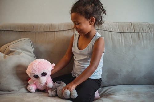Smiling little Hispanic girl playing with soft toys on cozy sofa in living room