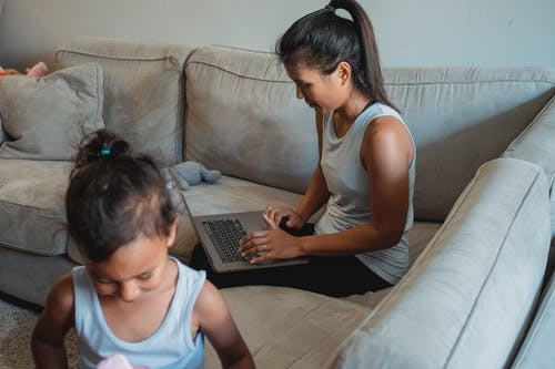 Adult ethnic woman using laptop while sitting on sofa with little daughter playing with toys at home