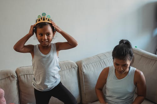 Smiling daughter wearing crown on sofa while mother sitting in living room