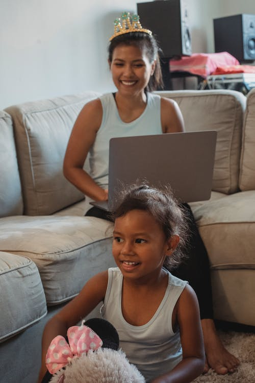 Ethnic mother with laptop looking at daughter