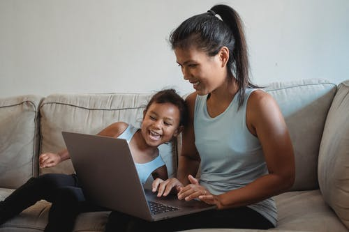 Ethnic mother and daughter with computer sitting on couch