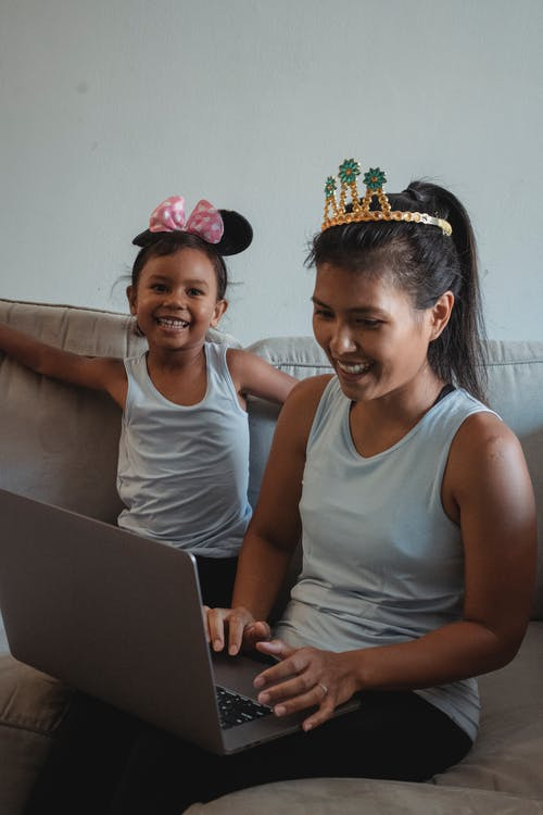 Ethnic woman using computer while kid playing
