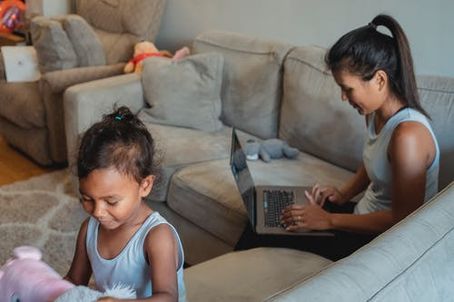 Adult mother using netbook for remote work while sitting on couch with little daughter playing with toys in living room
