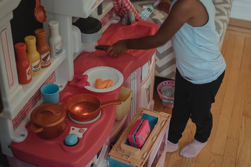 High angle crop unrecognizable ethnic child playing on small toy kitchen with plastic kitchenware
