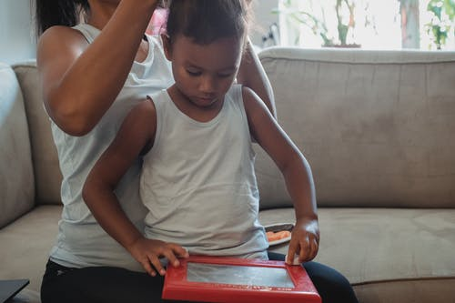 Crop woman in casual outfit sitting on couch and braiding focused little daughter playing with toy