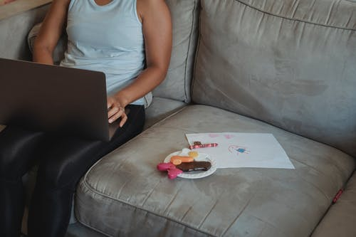 Crop mother using laptop on couch