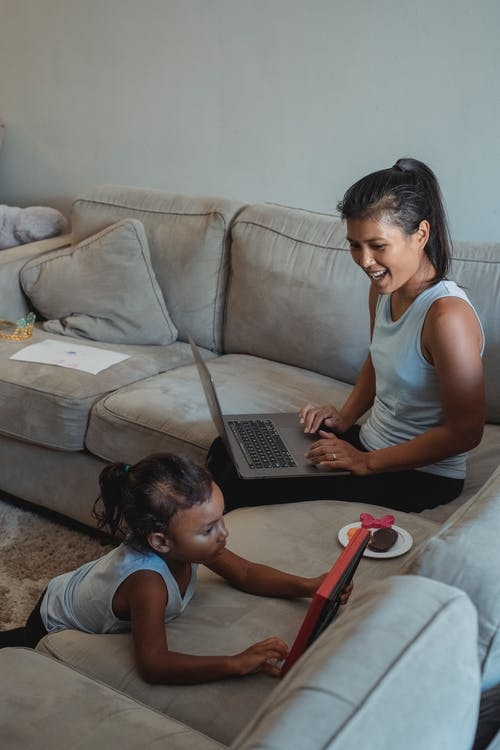 Ethnic woman with laptop looking at daughter