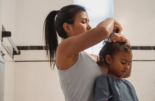 Side view of focused young Hispanic female in casual wear making hairdo for little daughter
