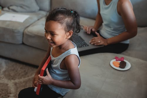 Ethnic girl with toy on sofa