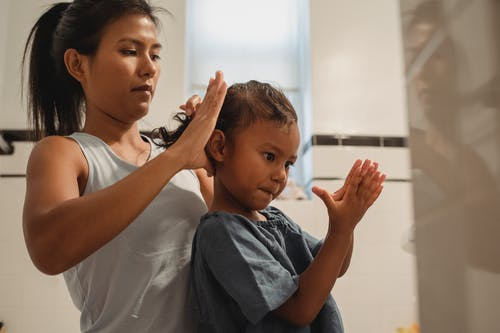 Side view of focused young Hispanic mother braiding hair of cute little girl