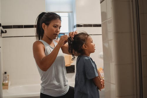 Side view of young Hispanic female in casual outfit standing in bathroom and braiding little daughter