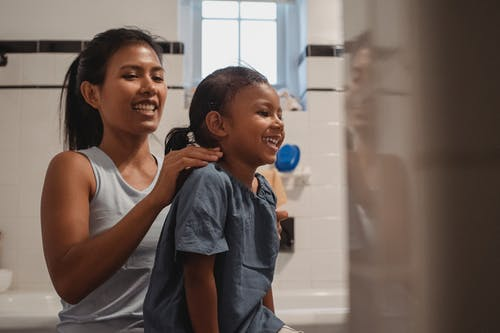 Happy young Hispanic female in casual wear brushing hair of adorable little daughter