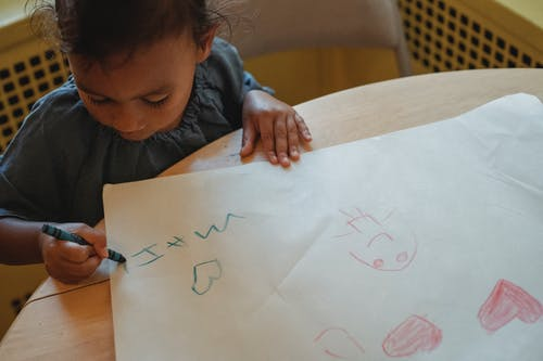 Little ethnic girl drawing at table