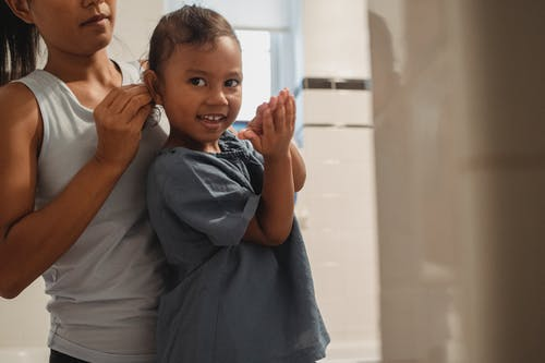 Crop anonymous young female in casual wear braiding cheerful little daughter looking at camera