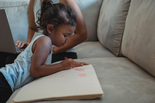 Concentrated ethnic girl drawing on paper