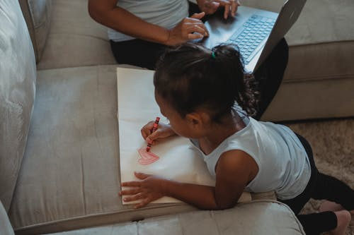 From above of ethnic little girl drawing on paper with wax crayon while mother using laptop sitting on sofa