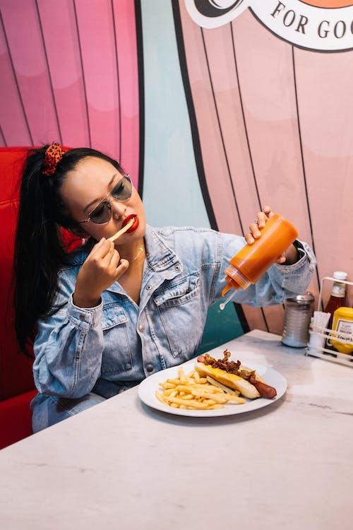 Woman in Blue Denim Jacket Drinking Orange Juice