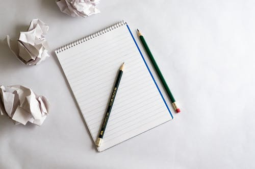 Pencil and Notebook over a White Surface