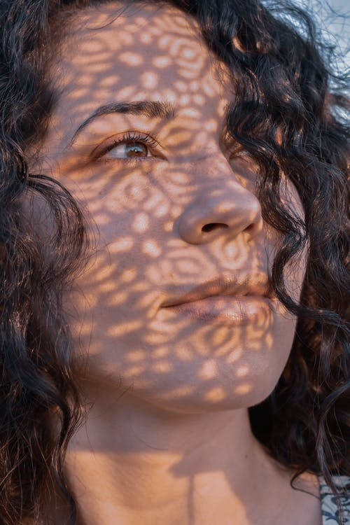 Woman with curly hair and shadows on face