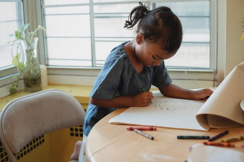 Concentrated Hispanic girl in casual clothes sitting at table and drawing picture with wax crayons