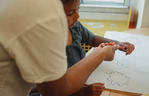 Crop mother and daughter drawing together
