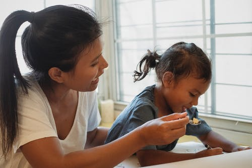 Mother feeding child at table