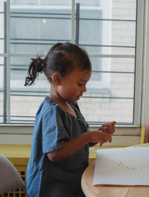 Side view of concentrated adorable little Hispanic girl drawing with color wax crayons while sitting at table near window