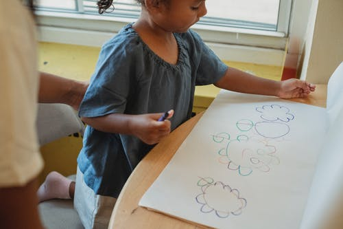 Crop focused child drawing at table
