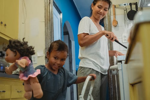 Cheerful little Hispanic girl playing with toys in kitchen while smiling mother standing near stove and cooking