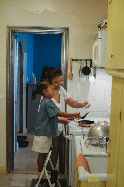 Smiling woman with daughter in kitchen