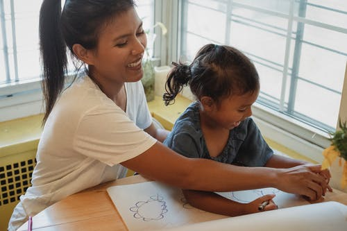 Happy Hispanic mother in casual outfit drawing together with adorable little daughter sitting at table