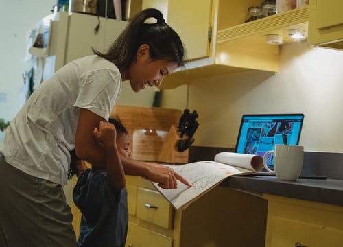 Side view of happy young Asian female in casual clothes pointing at drawing in sketchbook while spending time together with little daughter after work on laptop