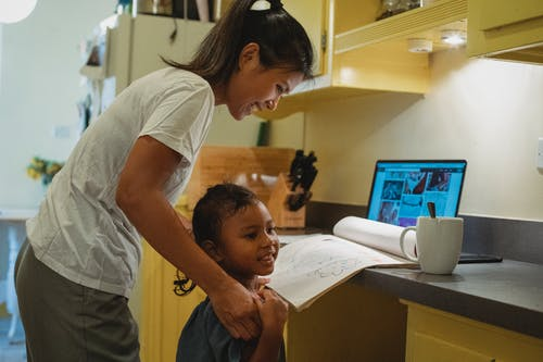 Side view of happy young Asian female freelance in casual clothes teaching little daughter to draw while working remotely on laptop at home