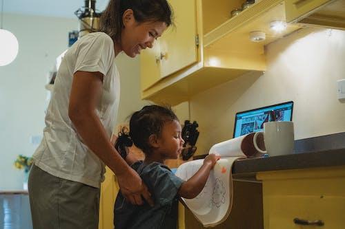 Glimlachende Jonge Aziatische Moeder Die Dochter Helpt Met Tekenopdracht In Keuken