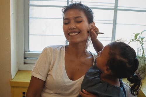 Cheerful ethnic little girl drawing on cheek of young mother with crayon