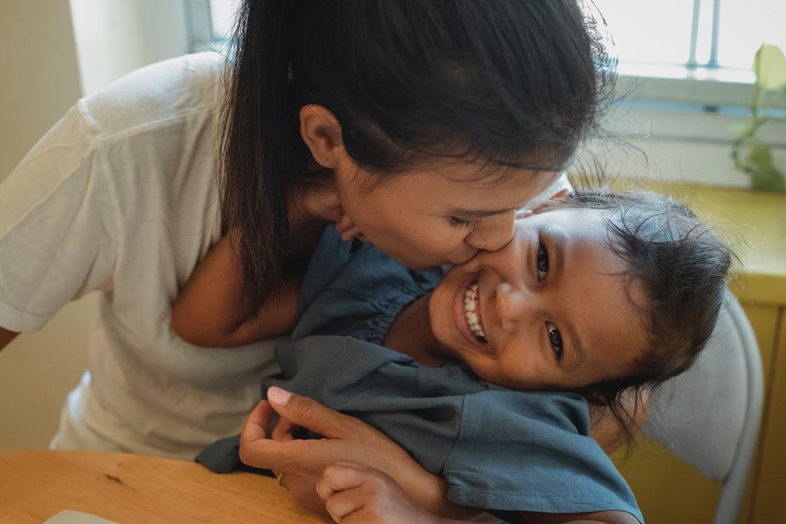 From above of happy young Asian lady hugging and kissing cheek of joyful little daughter while sitting together at table at home