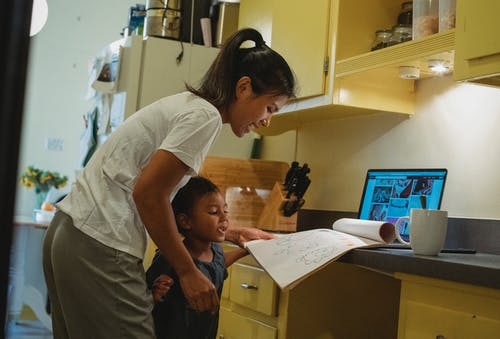 Delighted young Asian mother and little daughter doing homework together in kitchen