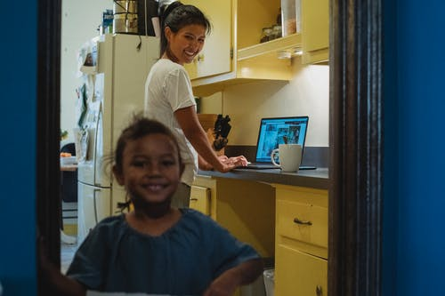 Cheerful ethnic woman browsing laptop in kitchen with positive little Asian girl standing in doorway and looking at camera in cozy apartment