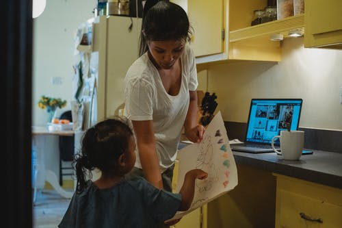 Unrecognizable little ethnic girl demonstrating paper sheet with drawing to mother while standing in kitchen with laptop and cup of drink