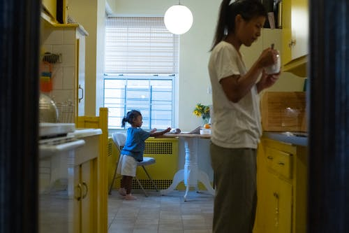 Side view of ethnic woman with cup of hot drink standing near cupboards in kitchen with little girl at table