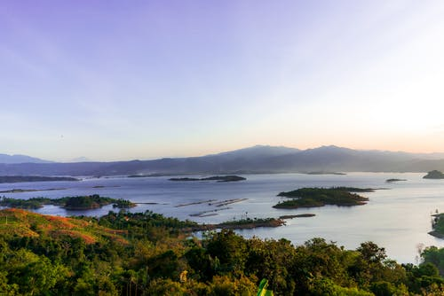Calm sea surrounded with hills covered with lush tropical vegetation